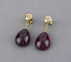 Yellow gold earrings composed of brilliant-cut diamonds in bezel setting at the earrings top part, and oval-cut cabochon ruby gemstones at the bottom part.