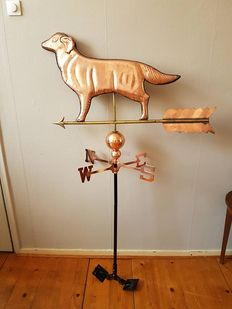 Large red copper roof weather vane in the shape of a dog