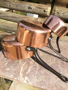Three red copper pans