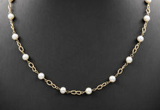Yellow gold necklace with 18 round cultured Akoya pearls.