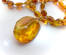 Genuine Baltic amber pendant necklace inlayed with 14 kt gold heart and topaz, weight: 21 gr.