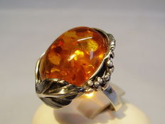Ring with large amber piece in floral setting