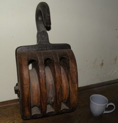 Antique large and heavy wooden pulley/wind up block with an iron hook.  3 wooden rollers of wood, they are still running good. All in good condition.