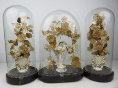 Three-part set of statue of Mary with Jesus and two matching vases with flowers under three bell jars