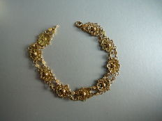 Gold bracelet consisting of 9 linked filigree rosettes.