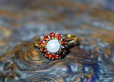 A 333 gold ring with a cultivated pearl and 10 garnets