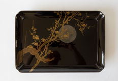 Black painted salver. Decorated with maki-e gold painted cherry blossom in front of a silver painted moon. In matching storage box – Japan – early 20th century (Taisho period)