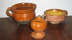 Lot of 3pcs 17th century household goods. Cooking pot on 3 legs and with 1 ear, height 120 mm, money box, height 115 mm. Porringer on stand ring, height 75 mm