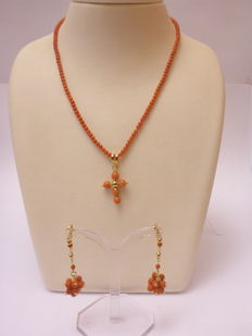 Red coral with gold necklace, ear studs and cross.