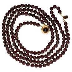 Necklace of glass garnet beads with yellow gold, decorative clasp of 14 kt.