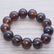 Baltic amber bracelet composed of  beads in cherry and coffee colour with blue tones. Weight: 26.20 g