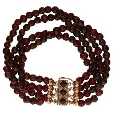 Bracelet of glass garnet beads with yellow gold, decorative clasp of 14 kt.