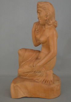 Wooden statue of a woman in half kneeling pose - Bali - Indonesia