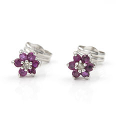 Star-shaped white gold earrings set with inlay of brilliant cut diamonds and ruby.