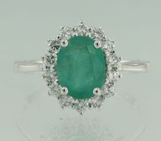 White gold entourage ring of 14 kt set with a centre oval cut emerald of in total approx. 2.20 carat and 14 brilliant cut diamonds of in total approx. 0.60 carat