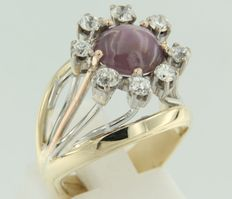 Bi-colour gold entourage ring of 14 kt set with a central cabochon cut star amethyst and an entourage of bolshevik cut diamonds ***No reserve price***