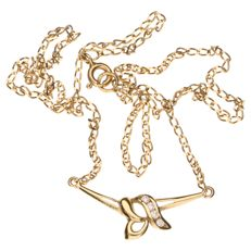 14 kt yellow gold link necklace with a pendant set with 4 white zirconia stones.
