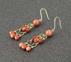 Long yellow gold earrings set with natural Pacific coral beads.