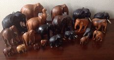 Collection of 21 large hand-carved wooden elephants.