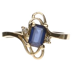 10 kt yellow gold wavy ring set with a princess cut sapphire and 2 zirconias