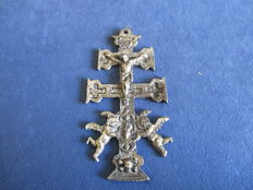 Double-cross-barred crucifix (Caravaca cross) , on which the figure of Jesus is flanked by two winged angels , in silver brass
