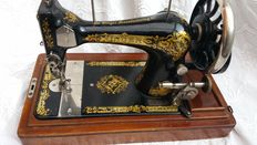 Antique Singer 28 sewing machine including wooden hood and key , 1910