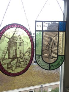 "Two beautiful hand-stained stained glass sun catchers ""Fruytier Maurice verwulgeis Romaijz"" and ""Molen en molenaar"", - 20th century."