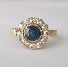 20s era ring with a sapphire surrounded by diamonds