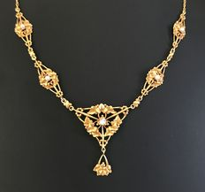 Drapery Art Nouveau necklace, decorated with 18 kt yellow gold ivy-shaped links set with fine pearls, and a central F/VS diamond in vertex.