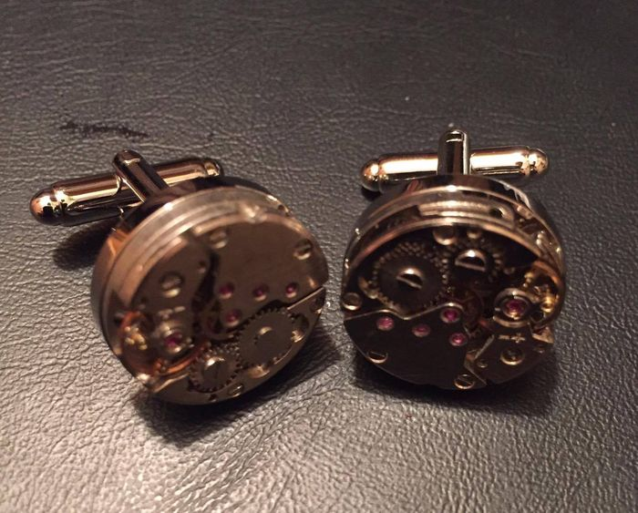 Cufflinks with a cutaway timepiece