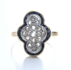 Two tone 18 kt gold Art Deco cocktail ring, set with calibrated sapphire gemstones and diamonds.