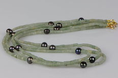A 3 row necklace made of natural serpentine drums with cultivated pearls.