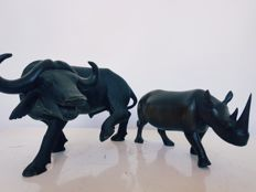NAIK. Pair of buffalo and rhinoceros figures carved in wood, 20th century