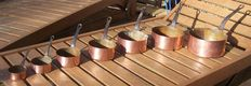 Vintage set of 7 graduated copper saucepans.