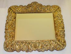Old mirror in a wooden frame with a copper finish.