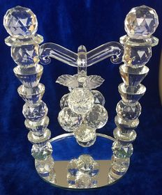 Facet cut large crystal temple with a hanging bunch of grapes on a mirror base