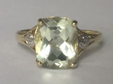 Gold ring with royal white-green topaz
