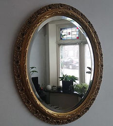 Oval faceted mirror with gilded baroque frame, late 20th century
