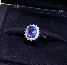 Blue violet topaz ring surrounded by diamonds in white gold setting