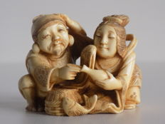 Ivory netsuke representing a divine couple signed with red seal - Japan - 19th/ early 20th century