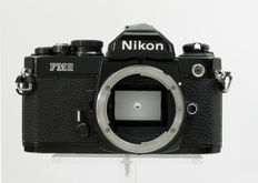 Nikon FM2N Black body with camera strap and body cap.