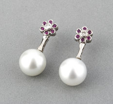 White gold flower shaped earrings with central diamond, rubies, and Australian South Sea pearls of 11 mm in diameter