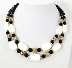 signed CORO - Two strand necklace. Beaded. Black, Ivory lucite & Gold tone Filagree beads. 1960s