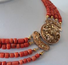 Necklace, consisting of four strands of red corals with a round, yellow gold hook clasp with springs.
