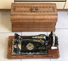 Antique Art Nouveau decorated sewing machine with original wooden case, inlaid with decorated wood types, Germany, ca. 1910.