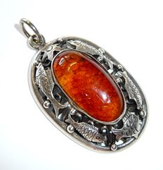 Antique pendant by GK Georg Kramer from around 1920, Baltic amber with a frame showing ocean motifs in 835 silver