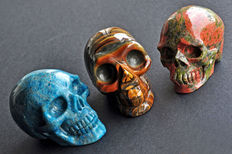 Fine trio of carved skulls - Unakite, Tiger's Eye and Apatite - from 7,4 to 7,9cm - 353gm (3)