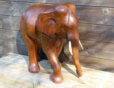 Large solid wooden elephant with bone tusks