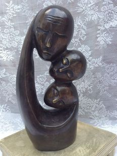 African bronze statue with three faces.