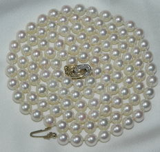 A pearl necklace made of Japanese Akoya salt water pearls, 6.8 mm diameters with a 585 / 14 kt gold clasp, 8 diamonds of 0.04 ct